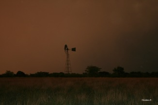 Windmill at sunset in the Kalahari with a storm brewing