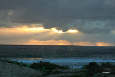 Sun bursting through the rainy clouds out at sea